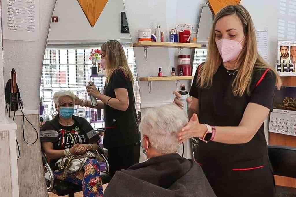 Maria Jesus Pavon ultimando el peinado realizado a una clienta - Peluquerías para quitarse el sombrero en Argamasilla de Calatrava